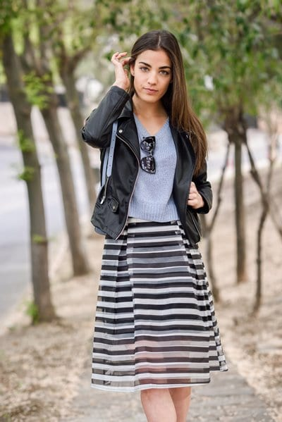 Portrait of young woman touching her hair with her hand in urban background wearing casual clothes. Girl wearing striped skirt, sweater and leather jacket