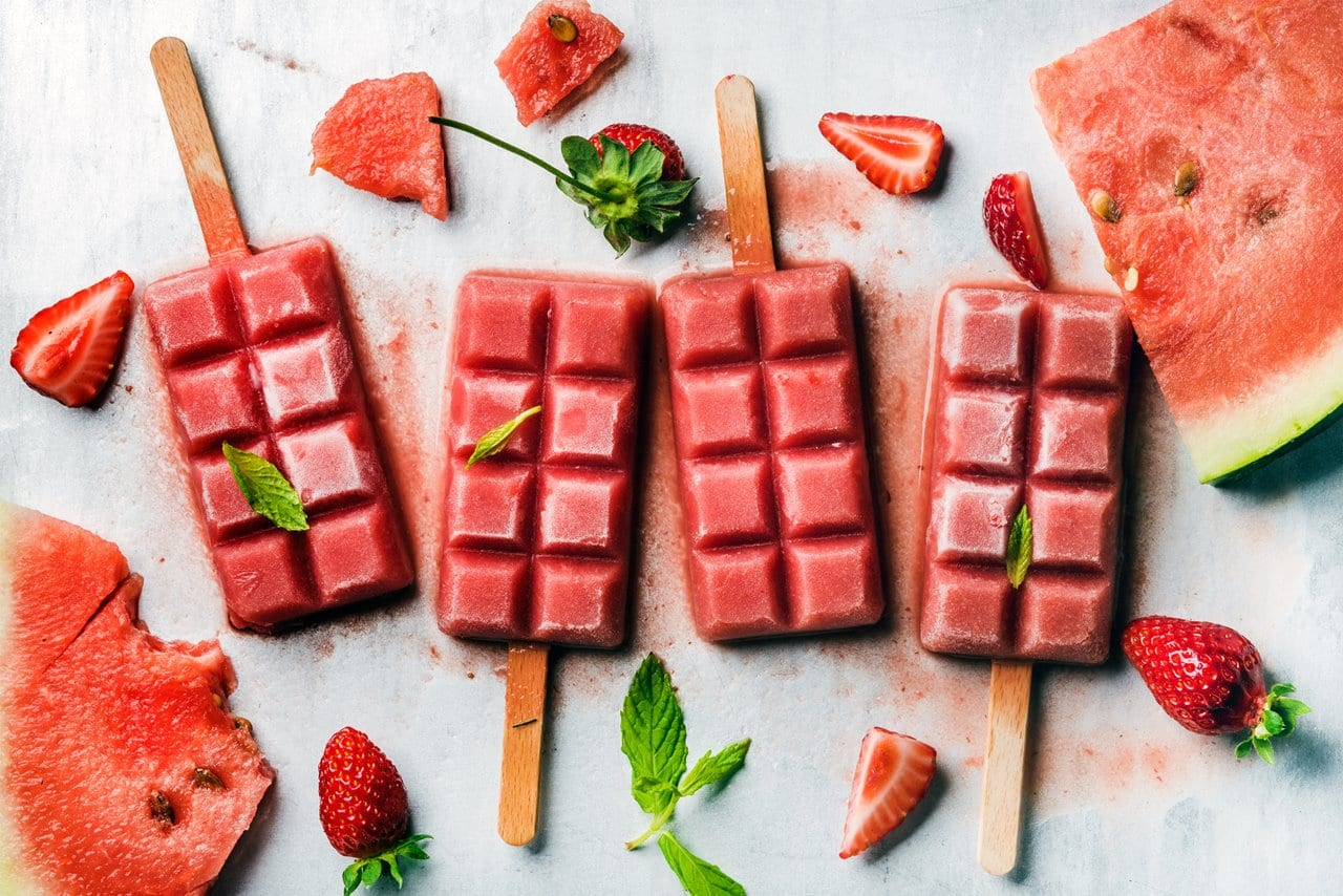 Strawberry watermelon ice cream popsicles with mint over steel tray